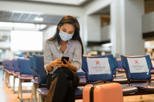 Young,Asian,Tourist,Woman,With,Mask,Using,Phone,And,Sitting