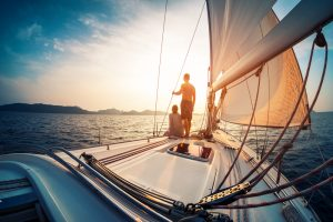 Couple,Enjoying,Sunset,From,The,Deck,Of,The,Sailing,Boat